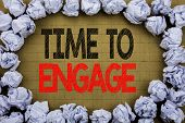 Time To Engage. Business concept for Engagement Involvement written on vintage background with space on old background with folded paper balls poster