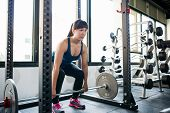 Asian athletic young woman doing deadlift exercise with barbell in the smith machine. poster