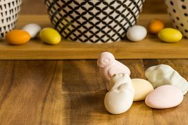 Colorful Easter Candy Eggs And Animal Shaped Marshmallows On Wooden Surface Besides Bowls With Black