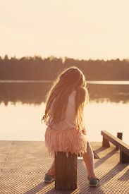Sad Beautiful Teen Girl Is Sitting  At Seaside During Sunset.  Back View