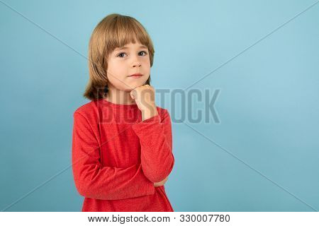A Teenage Caucasian Boy In A Red Jaket Thinks, Picture Isolated On Blue Background.
