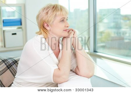 Portrait of friendly aged woman looking through the window