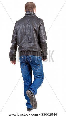 Volta vista indo homem bonito na jaqueta e calça jeans.  andar de cara jovem, de jeans e casaco. Traseira