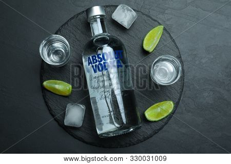 Mykolaiv, Ukraine - October 04, 2019: Absolut Vodka, Lime, Ice Cubes And Shot Glasses On Black Table