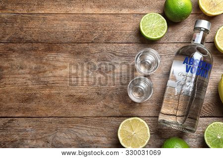 Mykolaiv, Ukraine - October 04, 2019: Absolut Vodka, Citrus Fruits And Shot Glasses On Wooden Table,
