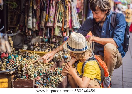 Dad And Son At A Market In Ubud, Bali. Typical Souvenir Shop Selling Souvenirs And Handicrafts Of Ba