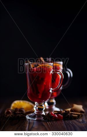 Christmas Hot Mulled Wine In Glasses With Spices, Cranberry And Orange Slices. Winter Warming Drink,