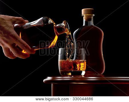 A Glass Of Whiskey On The Rocks And A Full Bottle Of Whiskey On The Wooden Table. The Glass Is Fille