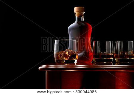 Two Glasses Of Double Whiskey And Ice On A Wooden Table. In The Background, A Closed Bottle Of Whisk