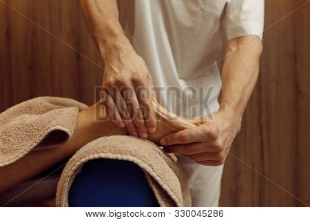 Male masseur pampering foot to woman, massage