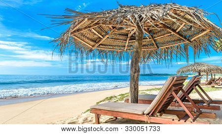 Tropical Beach On Blue Sky Background, Sri Lanka. Ocean And Nice Sandy Shore With Beach Beds And Umb