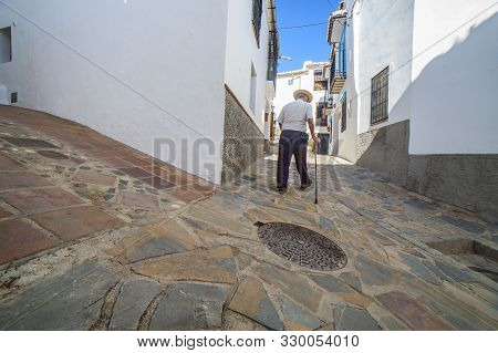 Elderly Local Man Climbing Slope Narrow Street Of Comares, Malaga, Spain. White Village Up On The Hi