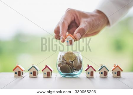 Business Woman Hand Holding House On A Coin In A Glass Bottle.concept Of Saving Money To Buy A House