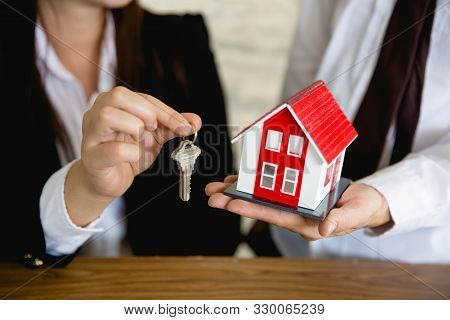 Red Roof House Holding Key And Houses By Businessmen.house In The Hands Of Businessmen Or Sales Repr