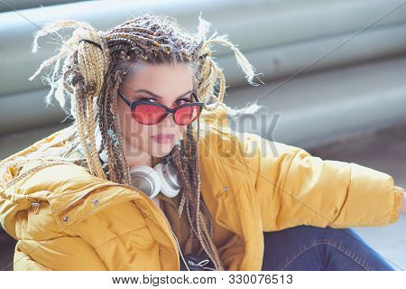 Portrait Of An Eccentric Modern Young Woman, Bright Make-up Sunglasses, And A Crazy Hairstyle. Cocky
