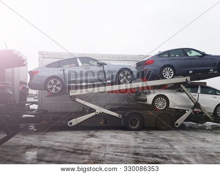 Loading New Cars From Conveyor Of Automobile Plant On The Truck For Delivery To Customers. Winter Su