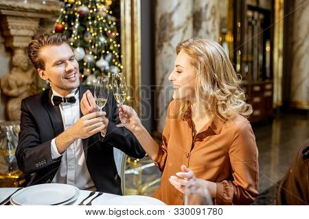 Elegantly Dressed Couple Having A Festive Dinner At A Well-served Table, Celebrating New Year Holida