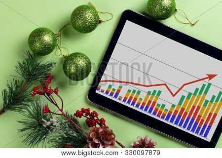 A Tablet With A Business Graph On The Desktop. Christmas Decorations.