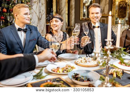 Elegantly Dressed Group Of People Having A Festive Dinner At A Well-served Table Near The Christmas