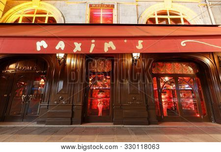 The Facade Of Famous Restaurant Maxim At Night, Paris, France.