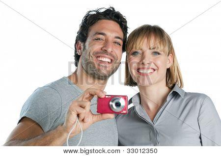Happy joyful couple taking pictures with digital camera isolated on white background