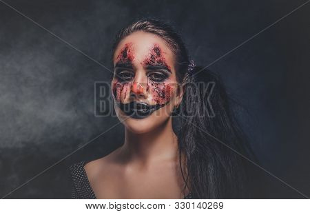 In Smoky Dark Photo Studio Woman In A Role Of Evil Clown Is Posing For Photographer.