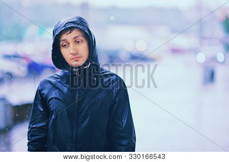 Wet Young Man With Unhappy Face Walks Along The Street During Heavy Rain, Close-up