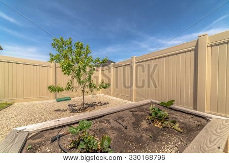 Close Uo Of Growbeds At The Backyard Of A Home With Tree Gravel And Fence