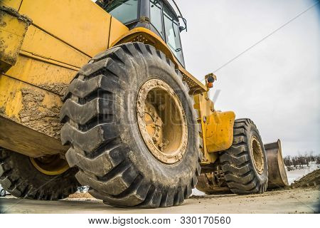 Focus On The Black Rubber Wheels Of A Yellow Bulldozer At A Construction Site