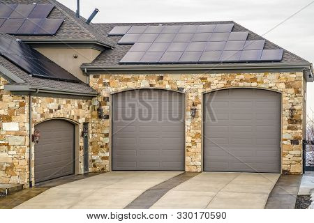 Home Exterior With Beautiful Stone Wall And Solar Panels On The Roof