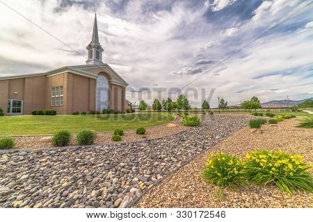 Sunny Day View With Cloudy Sky Over Church With Steeple And Large Arched Window