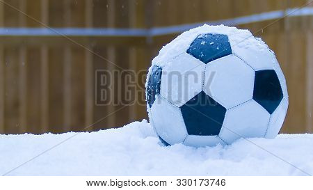 Football On Snow During A Winter Snow Storm With A Wooden Fence Background