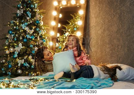 Lovely Mum Having Fun While Fighting Pillows With Her Daughters In Comfortable Home Interior, Friend
