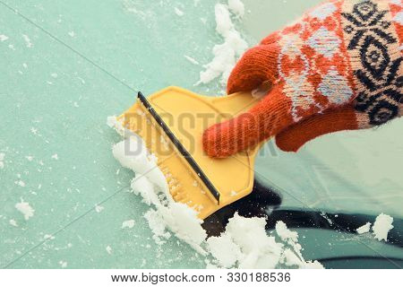Hand Of Woman In Glove Scraping Ice And Snow From Car Windscreen. Winter Problems In Transportation