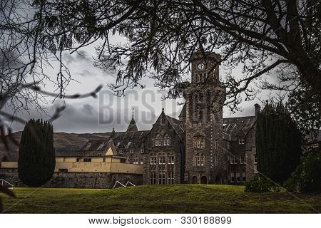 Fort Augustus, Scotland, December 17, 2018: The Abbey Highland Club Clock Tower, Full Of Mold And Li