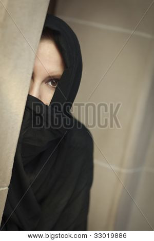 Cautious Islamic Woman in a Window Pane Wearing Traditional Burqa or Niqab.