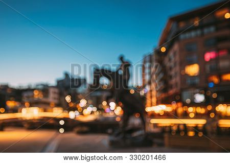 Oslo, Norway. Night Abstract Boke Bokeh Background Effect. Horse Statue On The Street And Residentia