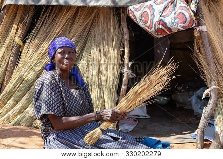 Old African woman in a village in Botswana standing in front of a shack in the bush, thatching grass
