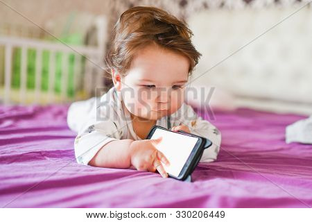 Child Addiction To Phones. Radiation From The Phone To The Child. A Little Boy 0-1 Years Old With A