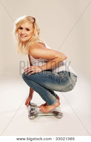 Slim and trim pretty blonde crouches low on a bathroom scale