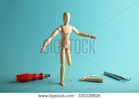 Wooden Figure Of Man With Artificial Prosthetic Leg. Amputee And Disability Concept.