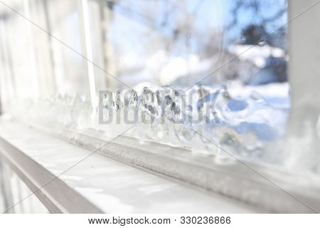 Ice forming on the inside glass of a drafty window in winter, shallow focus on ice