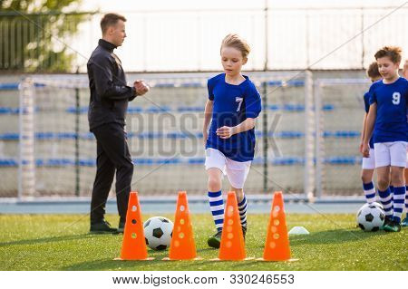 Young Happy Blonde Soccer Player Running With Ball On Training. Coach Of Youth Football Team Explain