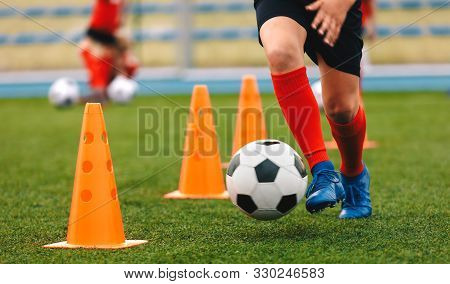 Footballer Dribbling Ball On Training Between Orange Cones. Young Football Player In Sports Blue Cle