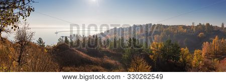 Steep Hilly Shore Of Reservoir With Gullies, Overgrown With Trees In Morning Haze In The Sun Backlig
