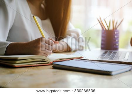 Woman Hand With Pencil Writing On Notebook. Making Notes In Notebook With Pencil. People Writing On