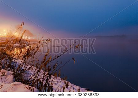 The River With Snow-covered Banks At Sunset Is Covered With Thick Fog