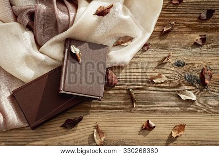 Pair Of Books, Light Stole On Wooden Table With Autumn Leaves. Top View. Concept Of Romantic Mood, R