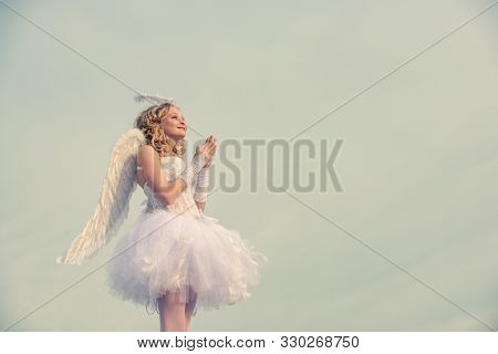 Charming Curly Little Girl In White Dress And Wings - Angel Cupid Girl. Portrait Of A Cupid Little G