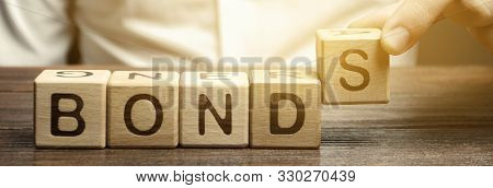 Businessman puts wooden blocks with the word Bonds. A bond is a security that indicates that the investor has provided a loan to the issuer. Equivalent loan. Unsecured and secured bonds. poster